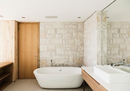 Salle d'eau avec murs de pierre et mobilier en teck
