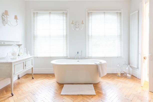 Salle de bain lumineuse avec beignoire et parquet