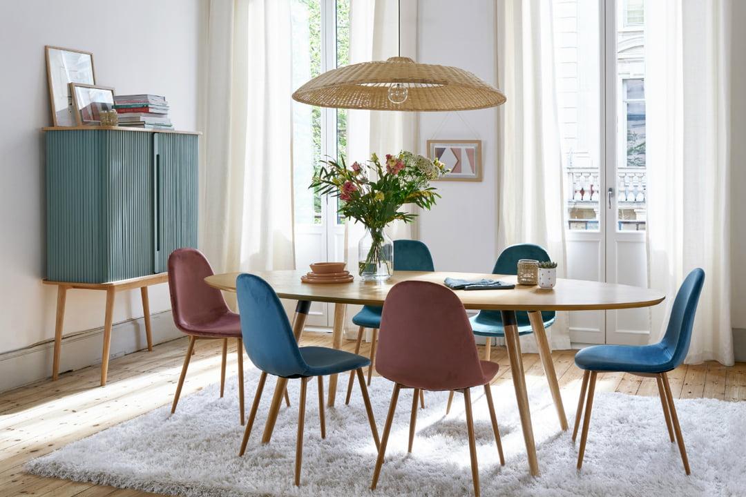 Salle à manger décorée de façon scandicraft avec des murs blancs, du mobilier en bois et du mobilier aux couleurs bleu et bordeau