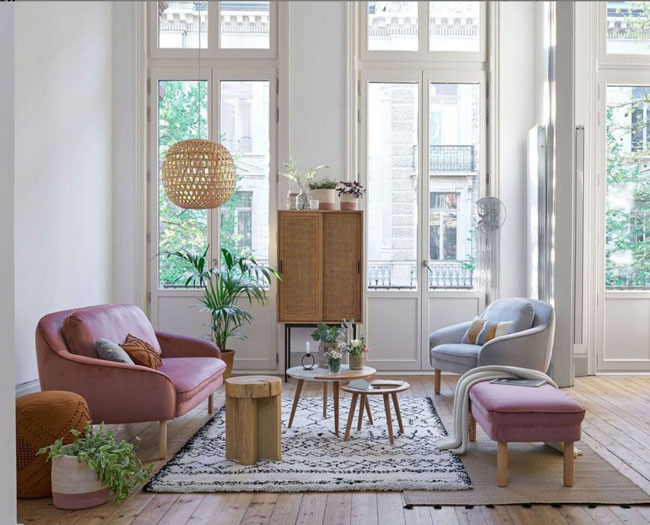 Salon d'appartement avec murs blancs et mobilier bordeau et bleu, luminaire en osier et touches de verdure