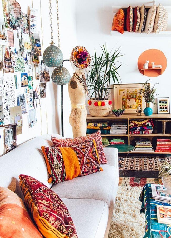 Salon décoré de façon bohème, avec un canapé blanc et des coussins rouges, des murs chargés de photos et des tapis colorés