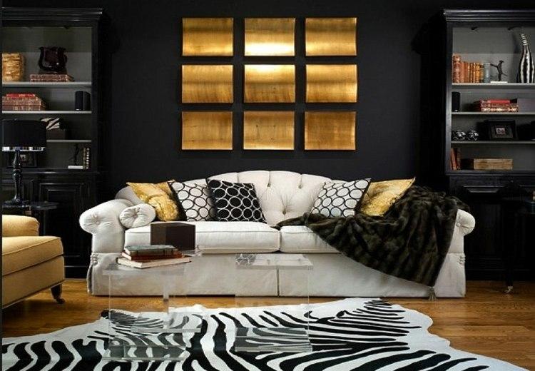 Salon avec mur noir, canapé blanc et accessoires dorés