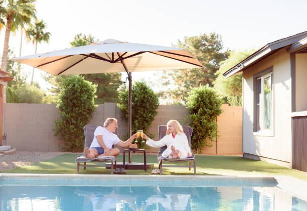 Parasol géant dans un jardin avec piscine, au bord de laquelle un coupe se repose sur des transats