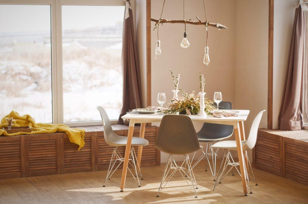 Petite salle à manger aux couleurs terreuses et un lustre en bois