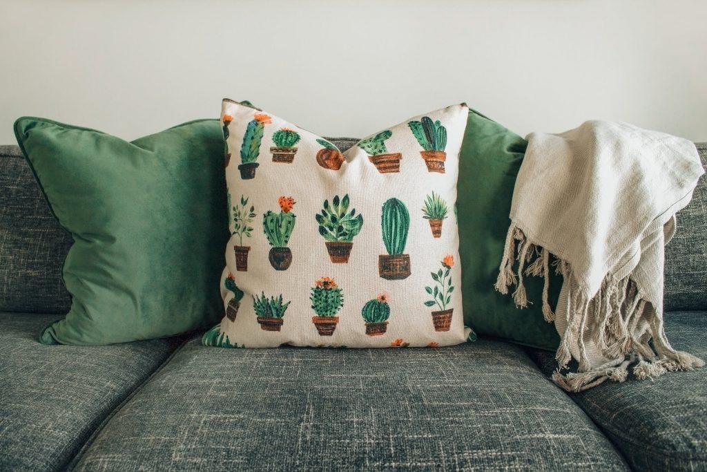 Coussins verts avec des motifs de plantes et couverture en lin posés sur un canapé