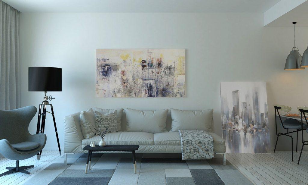 Salon moderne avec un canapé au centre, un tapis à motifs géométriques et un tableau au-dessus